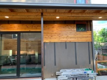 Thin black wood planks are spaced evenly directly onto exterior wall SIP Panels. These are what creates the air gap between the house and the Cedar Screen.